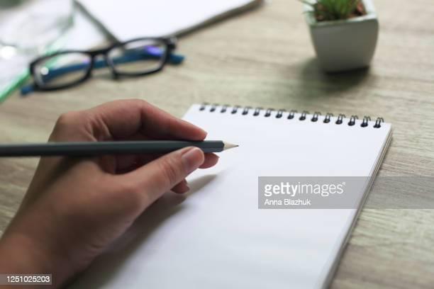 female hand with pencil writing in the notepad on desk. natural daylight. international lefthanders day. - linkshandig stockfoto's en -beelden