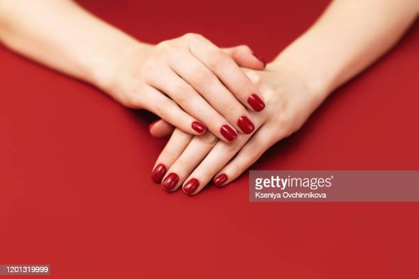 female hand with shiny red nails, manicure and nail care concept. - red nail polish stock pictures, royalty-free photos & images