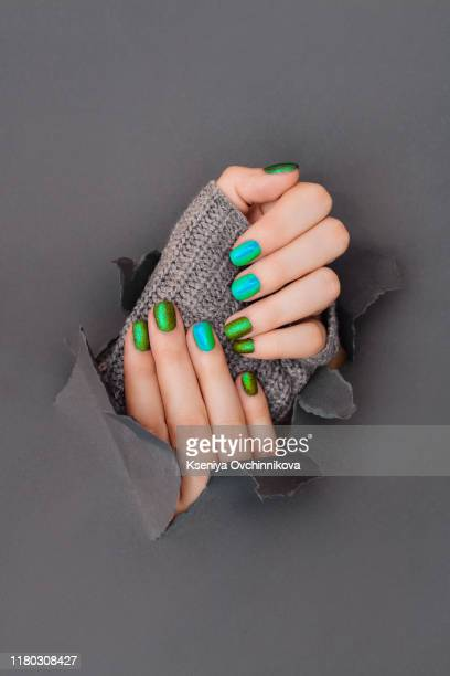 a female hand with spring green mint coloured nail polish on holding a twig against a green background - eco-friendly nail polish - nail art stock pictures, royalty-free photos & images