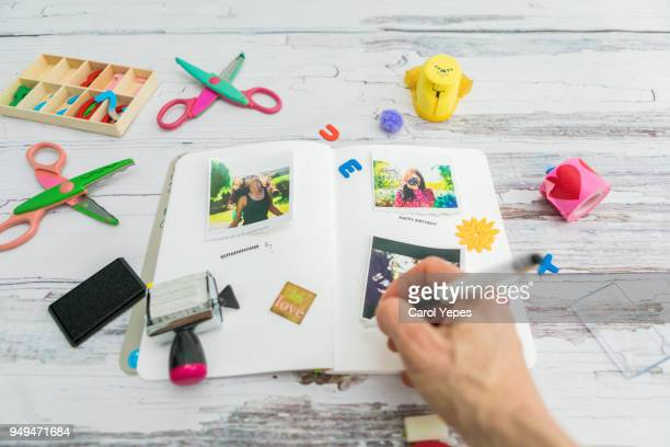 female hand writting in a  photo journal - photo album stock photos and pictures