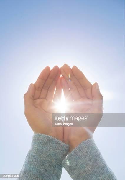 Female hands against clear sky, sun shining through fingers
