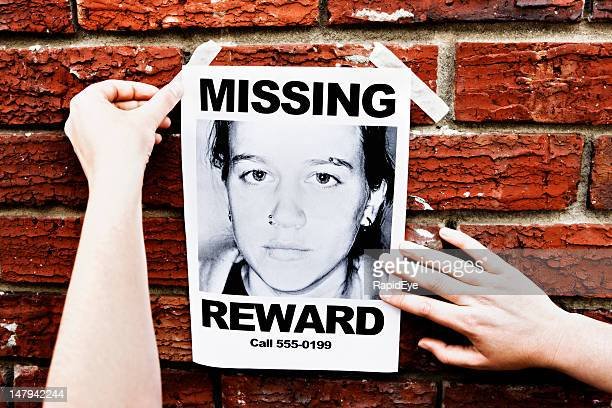 """female hands attach """"missing"""" poster of teenage girl to wall - lost stock pictures, royalty-free photos & images"""