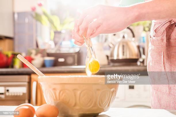 Female hands breaking egg in baking bowl.