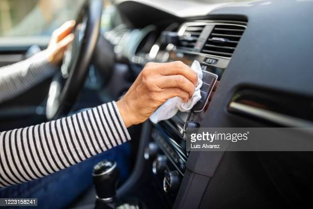 female hands cleaning and disinfecting her car interior - abstand halten infektionsvermeidung stock-fotos und bilder