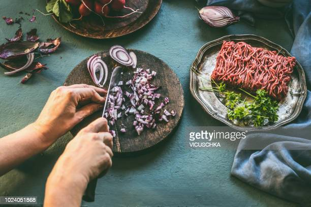 Female hands cut an onion on kitchen table with minced meat and ingredients
