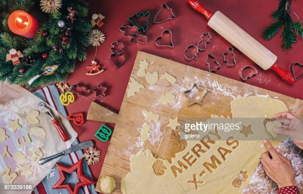 female hands cutting out christmas cookies - fotosession stock photos and pictures