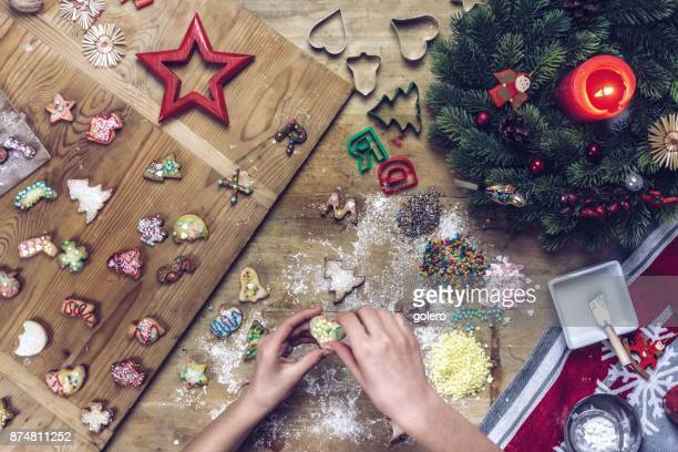 female hands decorating christmas cookie at wooden table - fotosession stock photos and pictures
