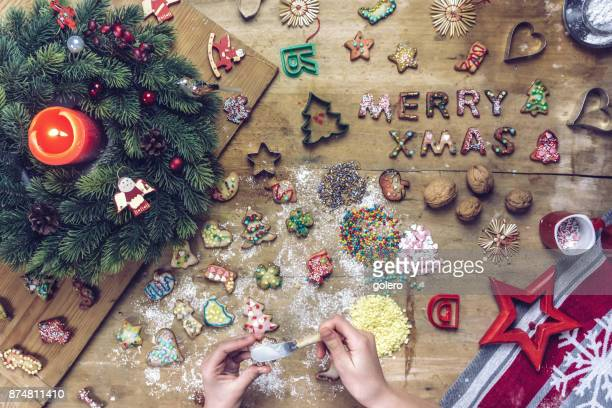 female hands decorating christmas cookie on rustic table - fotosession stock photos and pictures