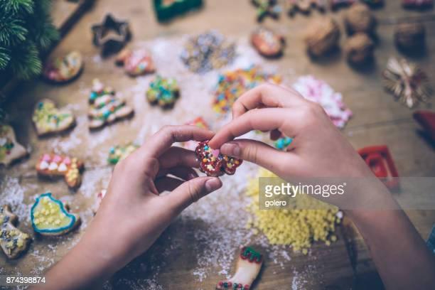 weibliche Hände Dekoration Weihnachtsplätzchen auf Holztisch
