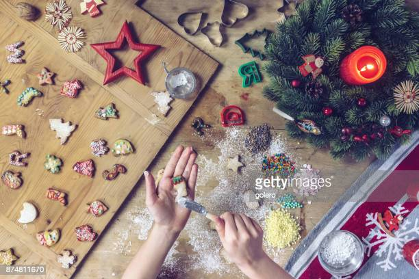 female hands decorating christmas cookie on wooden table - fotosession stock photos and pictures
