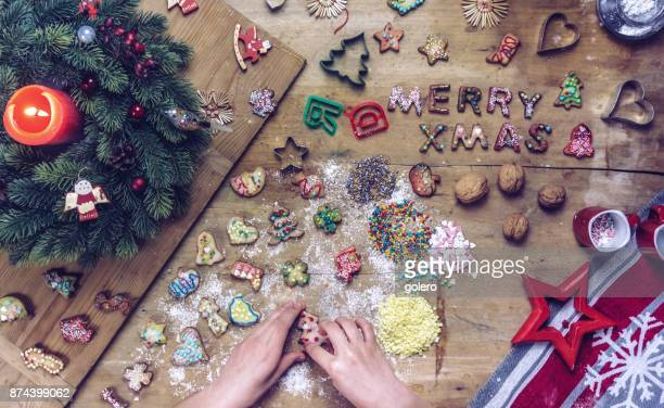 female hands decorating christmas cookies on wooden table - fotosession stock photos and pictures