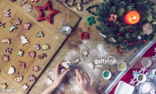 female hands decorating cookie heart on wooden table - fotosession stock photos and pictures