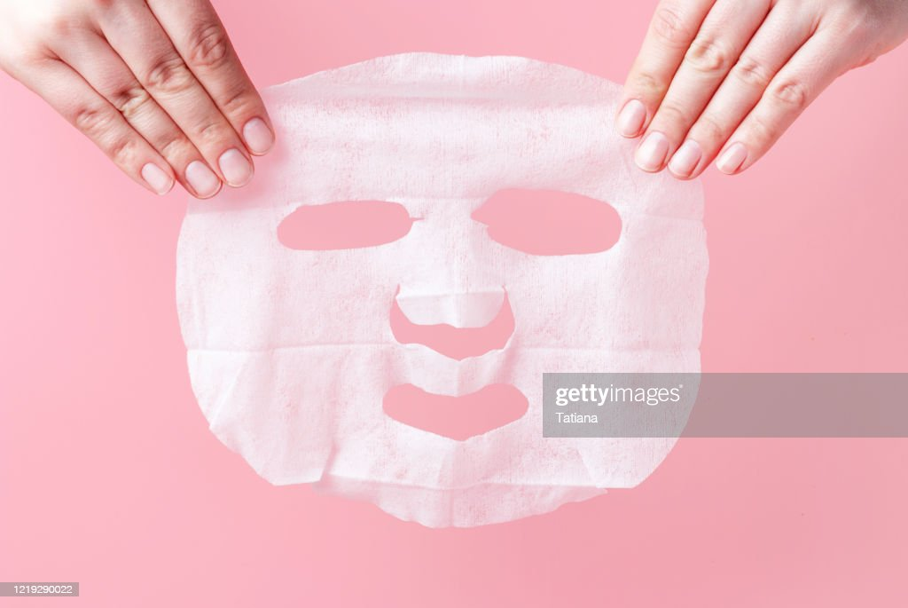 Female hands hold white fabric mask on pink background. : Stock Photo