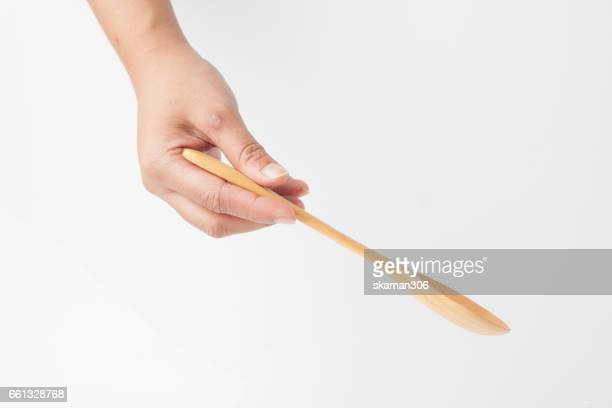 female hands hold wooden spoon  for cooking