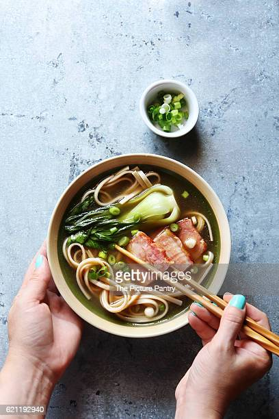 Female hands holding a bowl of pork belly udon noodle soup.Top view