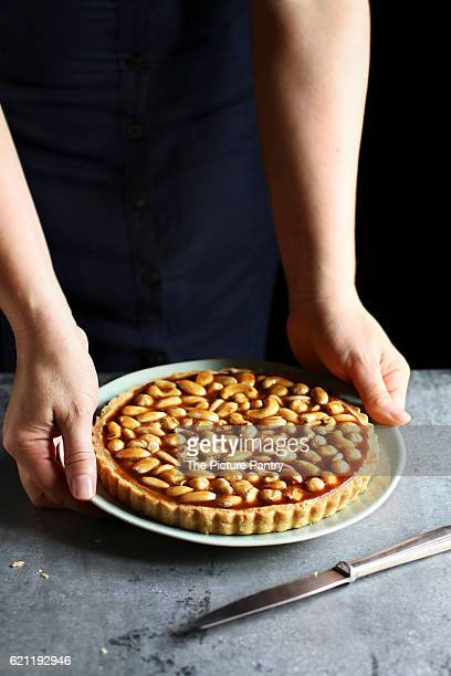 Female hands holding a caramel nut tart on a plate