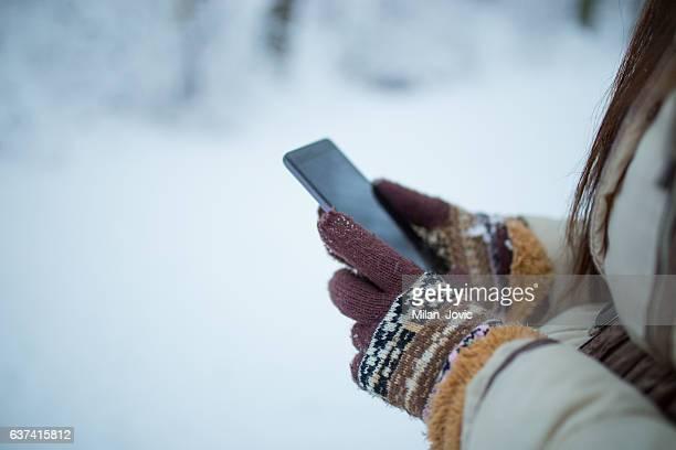 female hands holding a cellphone outdoors in the snow - handschoen stockfoto's en -beelden
