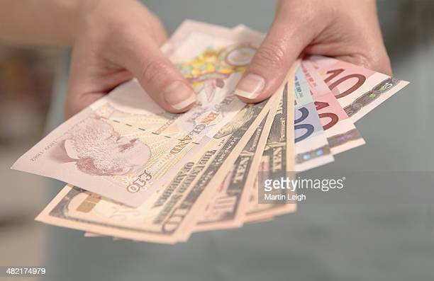 Female hands holding American, British and European currency