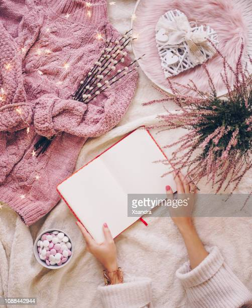 female hands holding an open blank notebook. coziness and comfort concept flat lay - flat lay stock pictures, royalty-free photos & images