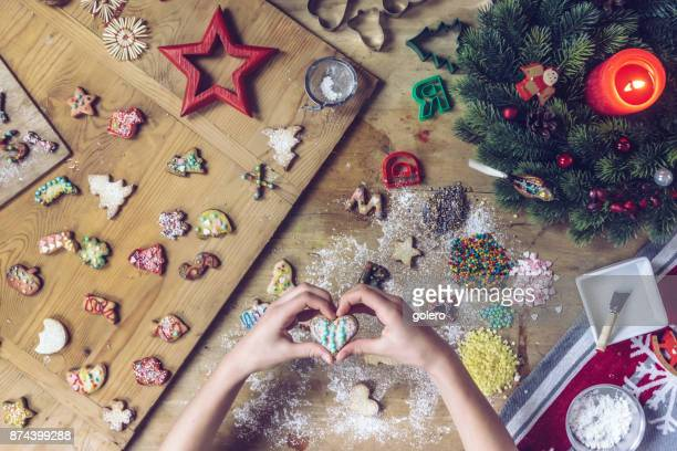 female hands holding candy heart over wooden table with christmas cookies - fotosession stock photos and pictures