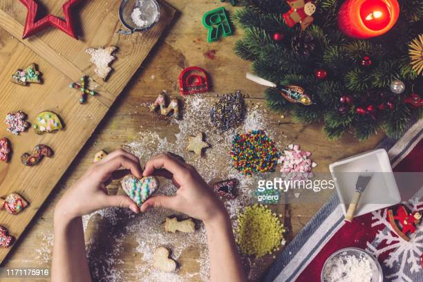 female hands holding christmas cookie of heart shape - fotosession stock photos and pictures