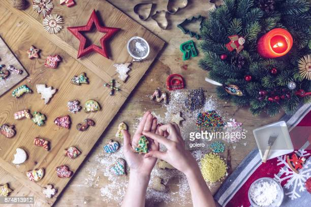 female hands holding christmas cookie over wooden table - fotosession stock photos and pictures