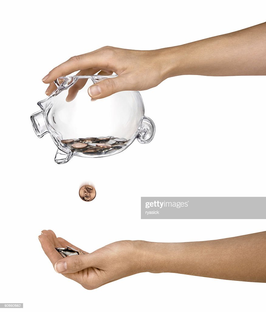 Female Hands Holding Clear Piggy Bank Shaking Out Coins Isolated : Stock Photo