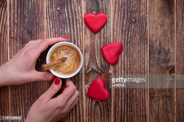 female hands holding cup of coffee on valentine's morning - lerexis stock pictures, royalty-free photos & images