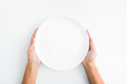 Female hands holding empty plate on white background 1084491202