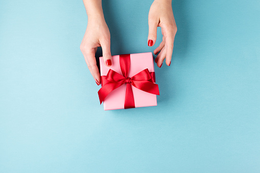 Female hands holding gift box on blue background. 1085197820