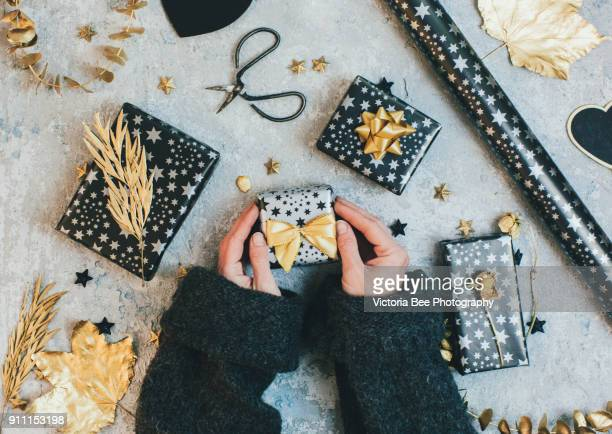 female hands holding gift boxes wrapped in black and gold paper on vintage background. - donna bendata foto e immagini stock
