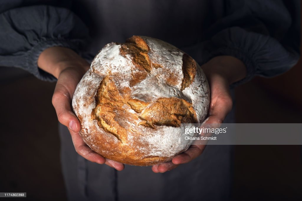 Female hands holding hot homemade baked whole wheat bread. : Stock Photo