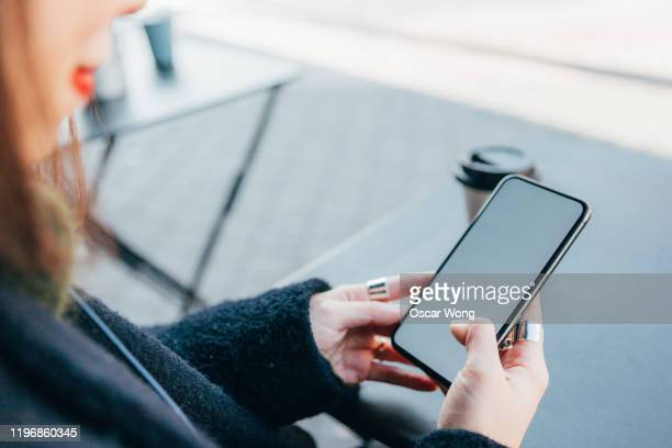 female hands holding mobile phone with a blank screen - hand stock pictures, royalty-free photos & images