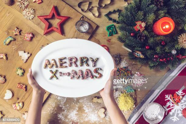 female hands holding plate with merry christmas letters made of cookies - fotosession stock photos and pictures