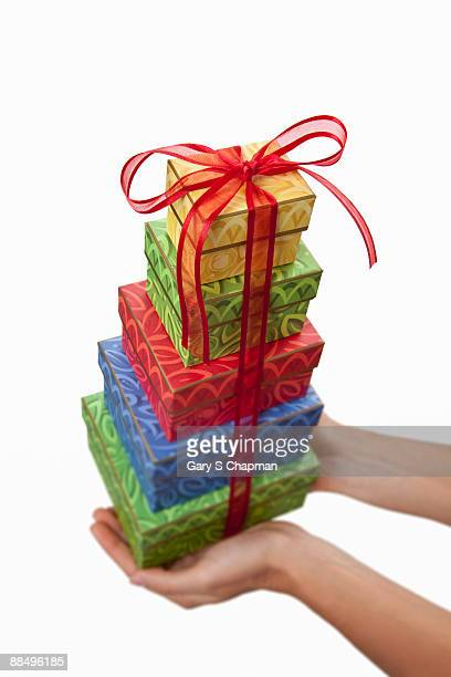 Female hands holding stack of colored gifts