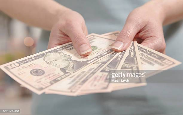 Female hands holding ten dollar notes