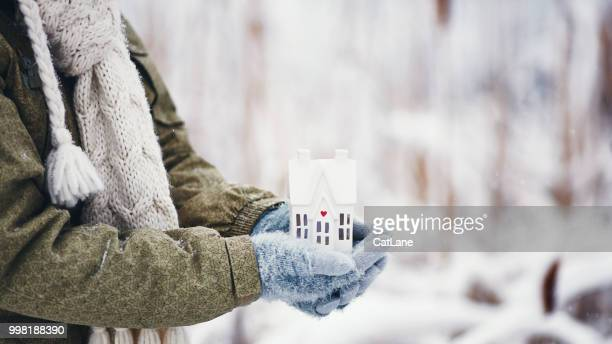 female hands holding tiny home in snowy weather - winter weather stock photos and pictures