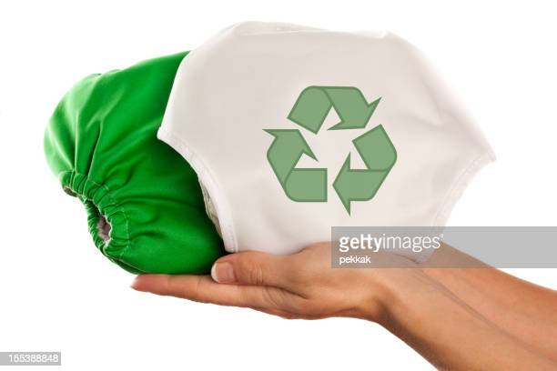 Female hands holding two cloth diapers one with recycling symbol