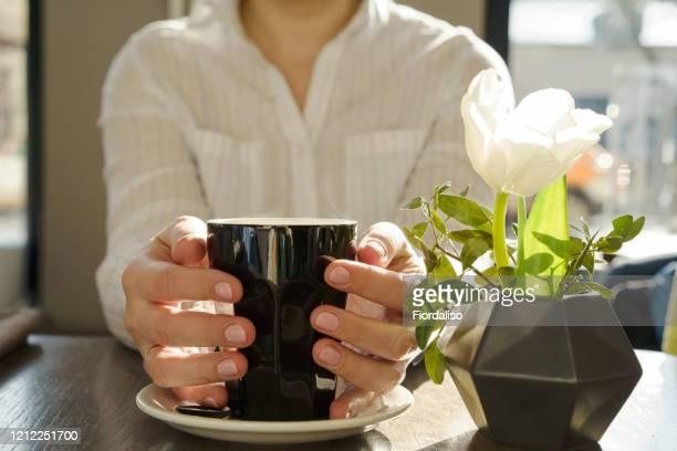 female hands hugging a big black cup with hot coffee. - hoja te verde fotografías e imágenes de stock