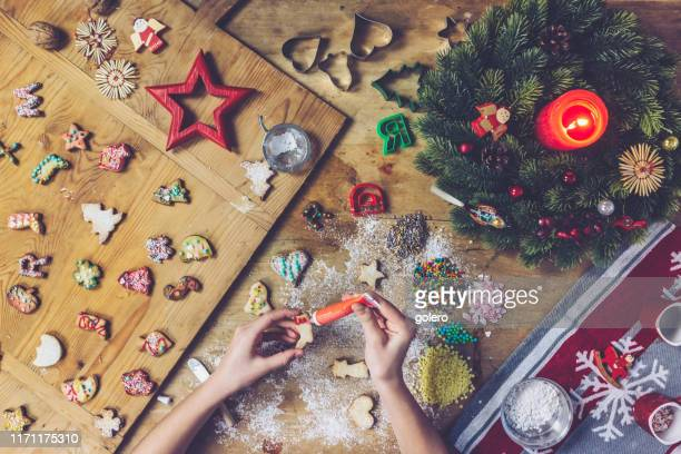 female hands painting christmas cookie - fotosession stock photos and pictures