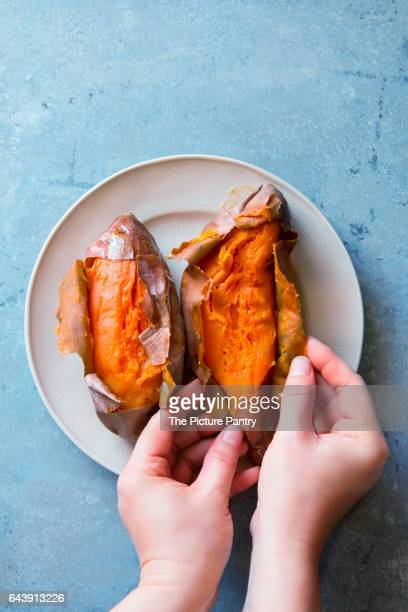 Female hands peeling freshly baked sweet poatoes.Top view