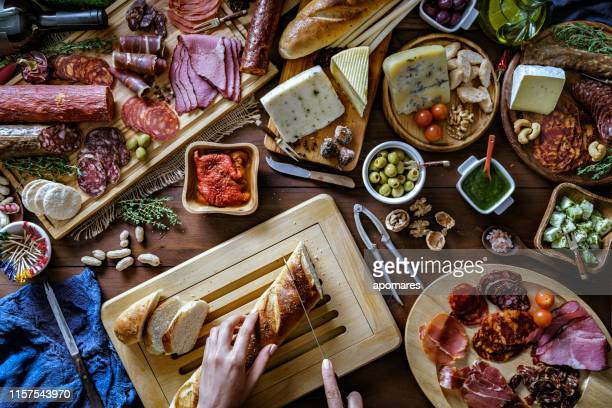 female hands preparing snacks and appetizers in a set full of assorted cured ham and cheese on rustic wood - antipasto stock pictures, royalty-free photos & images