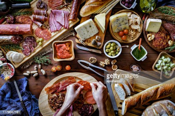 female hands preparing snacks and appetizers in a set full of assorted cured ham and cheese on rustic wood - salumeria stock photos and pictures