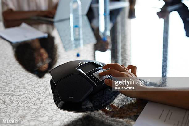 Female hands pushing digits on conference phone