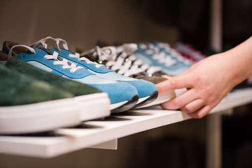 Female hands put sneakers collection on store rack 1134757670