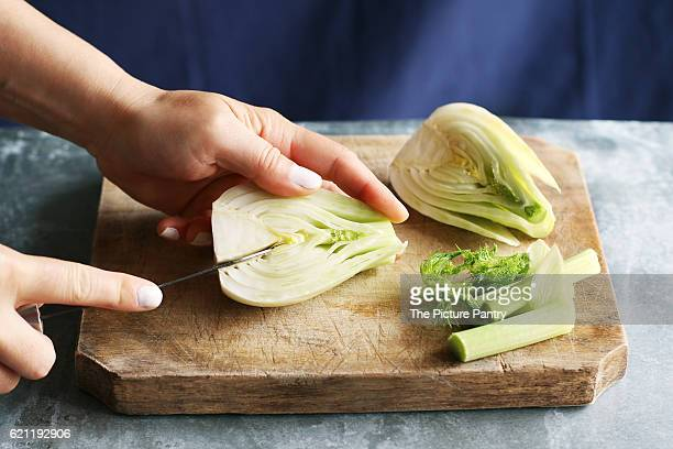 Female hands removing with a knife the tough core from a fennel bulb.