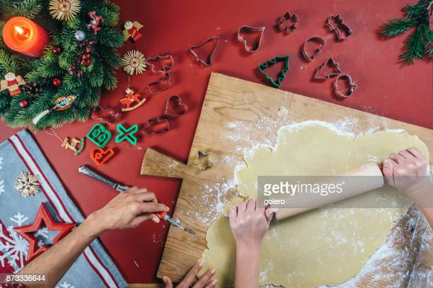 female hands rolling out dough for christmas cookies - fotosession stock photos and pictures