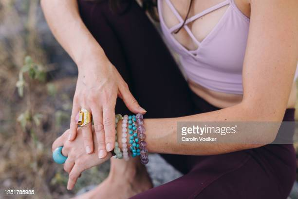 female hands touching each other wearing several rings and bracelets from precious stones and yoga pants - hands in her pants stock pictures, royalty-free photos & images
