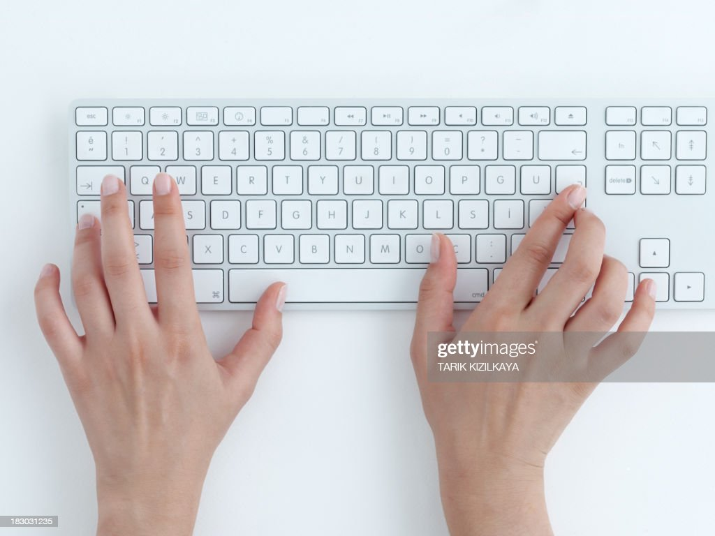 Female hands typing on a white computer keyboard : Stock Photo