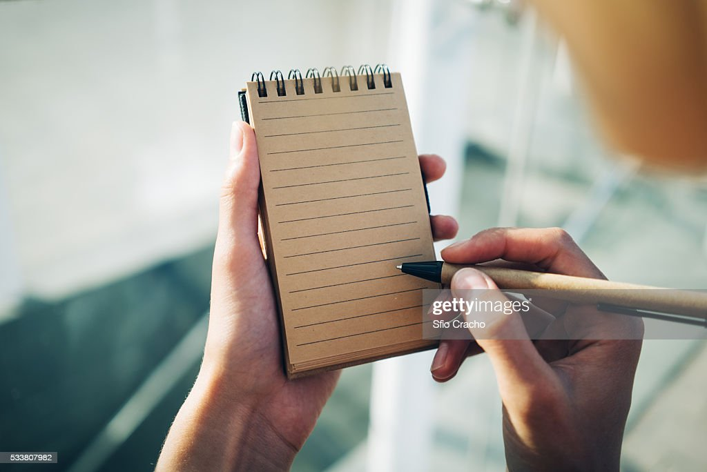 Female hands with pen writing in notebook : Foto stock